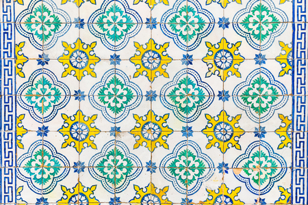 Azulejos tiles on a wall in Lisbon. Decorative tiles typical in Spain and Portugal on exterior walls. Texture and background with arabesque style