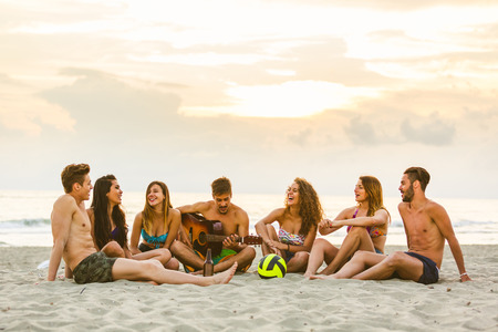 Group of friends singing on the beach. Multicultural group of teenagers and young adult people having fun at seaside. They are talking and playing guitars together. Summer and vacations concepts photo