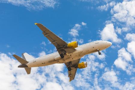 De bodemmening van het vliegtuig met wolken en hemel op achtergrond. Mening van een vliegtuig die op een zonnige dag landen. Reis-, transport- en reislustconcepten. Stockfoto