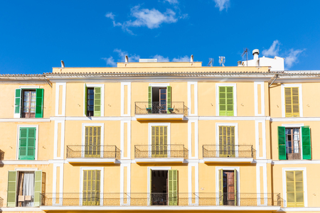 Apartment building facade with colourful shutters in Majorca. Typical mediterranean architecture and colors. Summer travel and vacations concepts Stock Photo