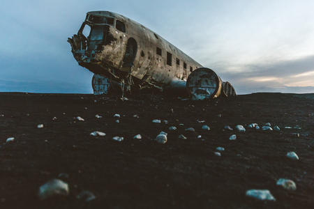 Iceland, Airplane wreck at Solheimasandur. Old and abandoned airplane, crashed on the black beach, at dusk, with nobody around. Travel and transport concepts.