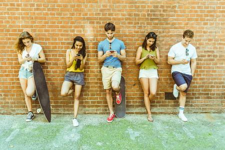お互いに興味がないのスマート フォンを使用しての友人のグループです。5 人の壁にもたれて、自分の携帯電話を見て友人を無視します。技術と実際の生活で社会的なメディア中毒です。 写真素材 - 82552727