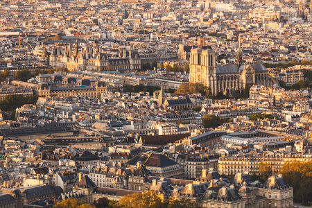 Paris, Notre Dame cathedral aerial view at sunset. Panoramic view of the famous church in Paris, with buildings and rooftops all around. Architecture and travel concepts