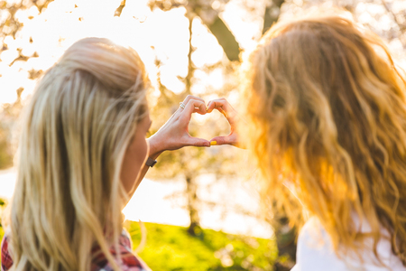 Lesbian couple making a heart with their hands while bonding together at park. Two women shot from the back over the shoulders. Love and lifestyle concepts photo