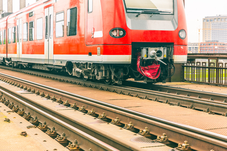 Train and railway tracks closeup. Regional red train in Germany with empty tracks on foreground. Transport and travel concepts.