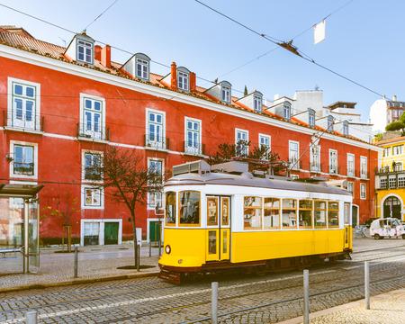 建物の背景に赤でトラム 28、晴れた日にリスボンで有名な黄色いトラム。ポルトガル、トーンのイメージから夏のはがき。旅行およびアーキテクチ