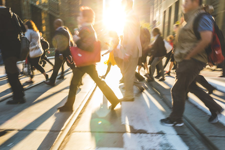 Blurred people crossing the street. Background ready image with fast moving people walking across the road in Toronto with sun flares in the middle. Travel and commuting concepts 写真素材