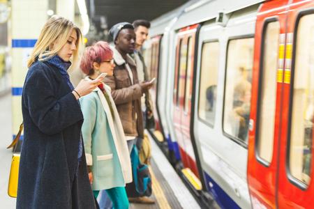 地下鉄の駅で電車を待っている人。混血者、2 人の男性およびラインに滞在し、電車に乗るを待っている二人の女性。通勤と交通