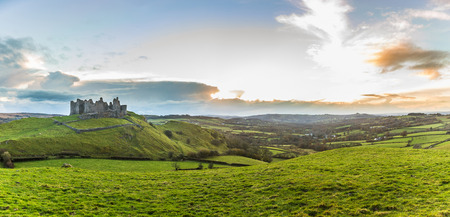 Countryside panorama with ruined castle on a hill. Welsh scenery at sunset, panoramic photo, with green meadows on foreground. Nature and travel concepts