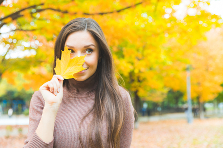 Portrait of a beautiful young woman hiding behind a yellow leaf. Smiling woman wearing turtleneck sweater with trees on background. Autumn season theme.