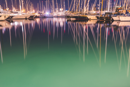 Sail boats and yachts in the harbour at night. Long exposure image of luxurious boats in Palma de Majorca. Focus on reflections. Travel and transportation concepts