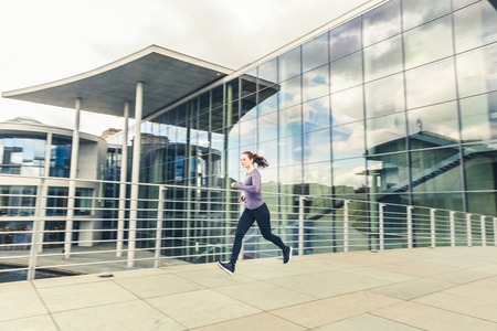 Woman jogging, panning view with modern buildings on background. Girl wearing hi-tech clothes doing fitness activities outdoors. Healthy lifestyle and sport concepts