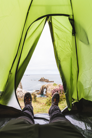 Cliff view from the tent with first person point of view pov. Man resting in the tent after hiking and looking out to seaside and nature. Travel and nature concepts Imagens