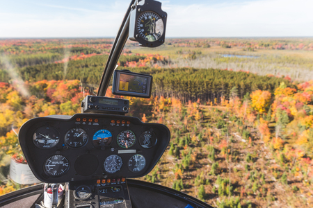 Helicopter cockpit in flight over autumn wood. Close up view of inboard instruments during a flight in Ontario, Canada, with a beautiful scenery. Nature and travel concepts