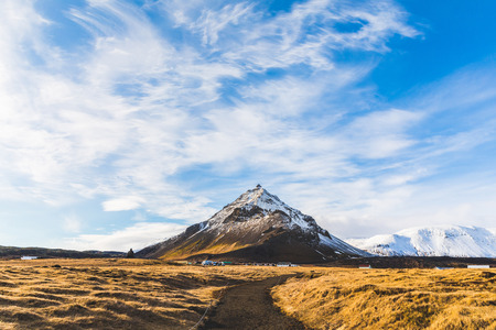 Mountain with snow in Iceland, winter landscape. Single mountain in the middle, clouds on top and yellow grass on foreground. Travel and winter concepts