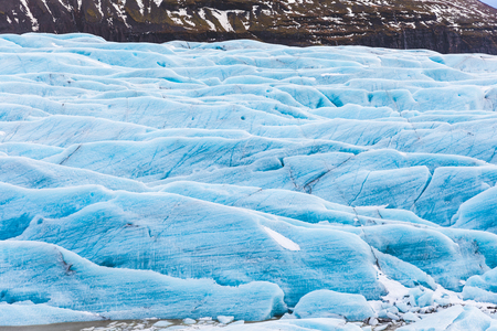 Glacier with blue ice close up in Iceland. Beautiful view of a glacier in the Vatnajokull area. Nature and textures.