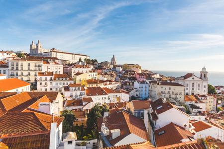 리스본 옥상 파노라마 화창한 날에. 주택과 교회와 포르투갈의 수도 도시의 다채로운 따뜻한보기. 여행 및 건축 개념