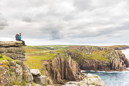 Man sitting on a rock cliff enjoying the view. Young man with backpack and hiking clothes on the cliffs over seashore in Cornwall, UK. Travel, nature and wanderlust concepts.