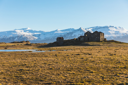 Iceland bleak landscape with ruined houses on foreground and snow covered mountains on background. Travel and winter concepts, wild Icelandic place.
