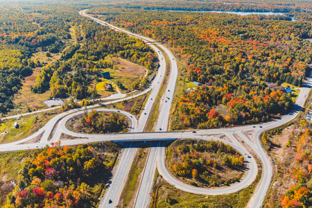 Highway junction aerial view in autumn. Photo taken in Ontario, Canada, from the helicopter during fall season. Colourful trees and wood. Travel and nature concepts