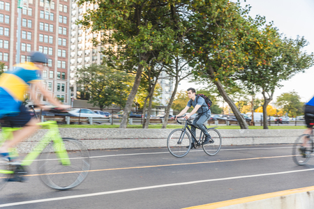 Man cycling in the city, panning shot. Young caucasian man commuting on his bike in Chicago. Urban outfit, travel and youth culture concepts. Stock Photo