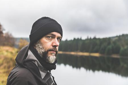 Mann mit Bartporträt im Freien im Herbst. Erwachsener Mann, der die warme Kleidung und den Wollhut trägt, der einen See bereitsteht und Kamera betrachtet.