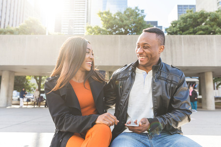 Black couple using phone and laughing. Man and woman sitting on a bench and looking each other, smiling. Lifestyle and happiness concepts Фото со стока