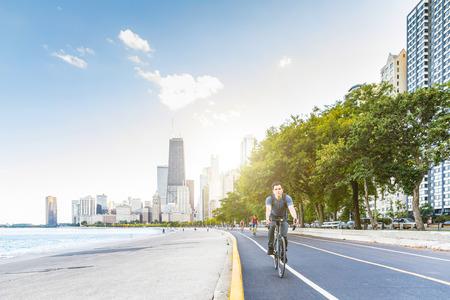 シカゴで都市を背景にサイクリングをする男。若い白人男性が自転車に乗って通勤している。都会的な服装、旅行、青少年文化の概念。