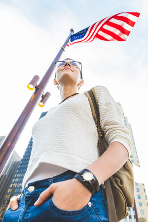 Young woman portrait in Chicago with USA flag on background. Woman with short hair and eyeglasses looking down, shyness and lifestyle concepts. Stock Photo