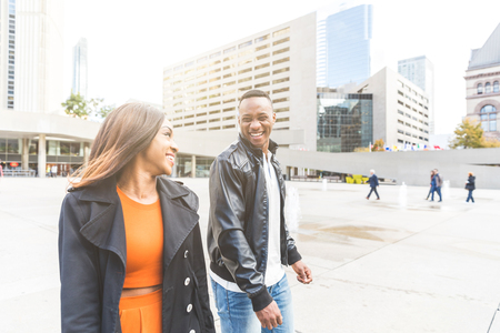 Black couple having fun in Toronto. Man and woman walking and laughing in the city during the day. Lifestyle and friendship or love concepts