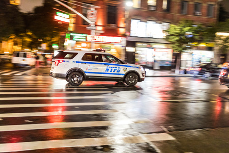 NEW YORK, USA - AUGUST 29, 2017: Police car rushing on the street, panning view with blurred background. NYPD car with emergency lights Editorial