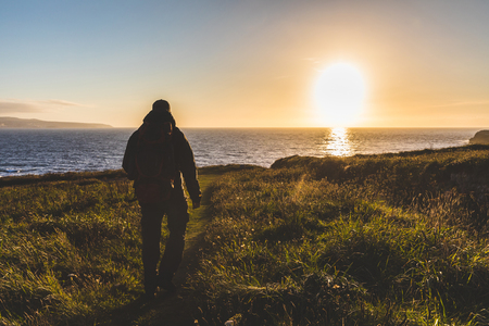 Man with backpack walking toward the sea at sunset. Explorer hiking over a cliff next to the seaside, backlight shot. Nature and adventure concepts. Imagens