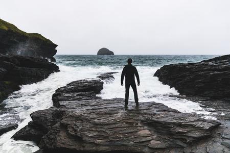 男向きの海と波の嵐の中に。水の横にある岩の上に立って、水平線を見て一人 写真素材