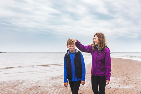 Brother and sister together at beach on a moody day. Siblings walking at seaside in autumn, annoying each other and having fun