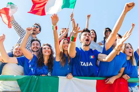 Italiaanse supporters die bij stadion met vlaggen vieren. Groep ventilators die op een gelijke en een toejuichend team Italië letten. Sport en levensstijl concepten.