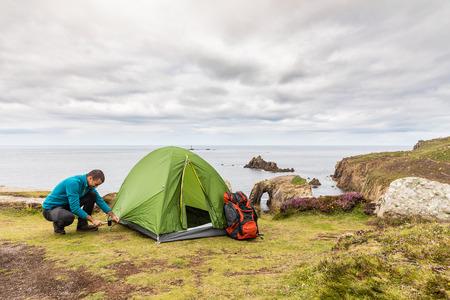 Mann richtete ein Zelt oben auf Klippen ein. Junger Mann, der einen Hammer verwendet, um die Stangen- und Abspannlinien einzustellen. Abenteuer Camping und Erkundung Standard-Bild - 86519203