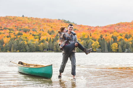 Happy couple after canoe trip at lake in Canada. Trees on background with colourful leaves during autumn. Young and happy, enjoying a canoe trip together. Wanderlust, love and nature concepts.