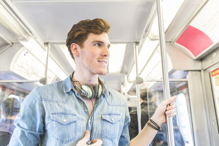 Young man on the train in Chicago. Portrait of a ginger young man wearing denim shirt and with headphones around the neck and travelling in the city