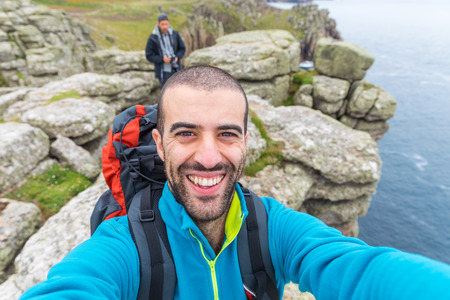 Man hiking and taking a selfie on top of cliffs. Young adventurer taking photos with fellow explorer and high cliff on background