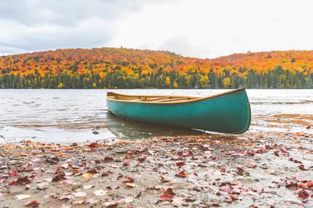 秋の自然の設定、湖の海岸にカヌー。カナダのアルゴンキン州立公園の美しいと静かなシーン