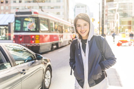 Smiling woman by the street in the city. Portrait of a young woman with short hair, wearing a hoodie and jacket, walking next to a busy road in Toronto. Travel and lifestyle concepts. Фото со стока
