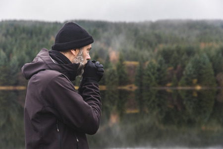Man with beard portrait outdoor in autumn. Adult man wearing warm clothes and wool hat standing by a lake and looking away.