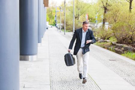 Homme d'affaires qui court dans la ville et regarde le regard. Homme caucasien à la fin de la cinquantaine, portant des vêtements décontractés intelligents et tenant une valise. Concepts de la vie d'affaires et de la ville. Banque d'images - 86519204