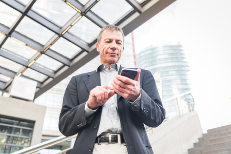 Businessman typing on his smart phone, modern city settings. Caucasian man on his late fifties, standing in a train station or a modern building, low angle view.