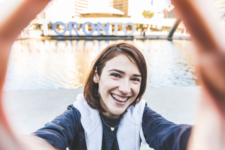 Happy girl taking a selfie in Toronto. Smiling young woman holding a camera and looking at it, showing a big smile. Toronto main square on background