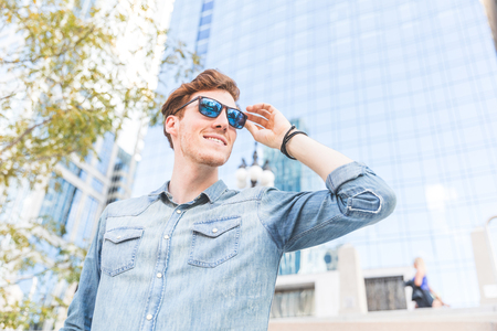Redhead man portrait on a sunny day in Chicago. Young man wearing denim shirt and sunglasses in the city, looking away from camera. Stock Photo
