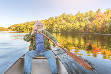 晴れた日に漕ぎカヌーと年配の男性。カナダ ・ オンタリオ州の湖でカヌーの男性。典型的な屋外活動、旅行、レジャーの概念