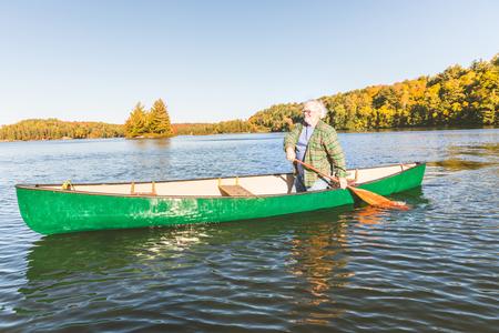 晴れた日にカヌー漕ぎをしているシニア男性。カナダ、オンタリオ州の湖でカヌーをする男。典型的な野外活動、旅行および余暇の概念