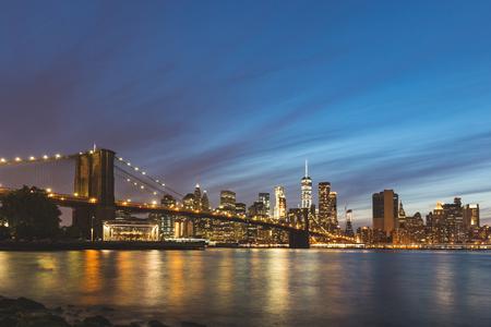 ニューヨーク、ブルックリン橋とダウンタウン夕暮れ時のマンハッタンのパノラマ ビュー。ライトアップされた橋や高層ビルの背景に長い露出イメ 写真素材