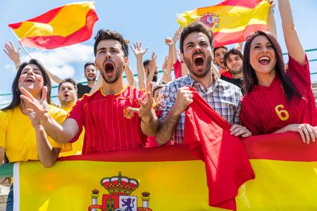 Spanische Anhänger, die am Stadion mit Flaggen zujubeln. Gruppe Fans, die ein Match aufpassen und Team Spanien zujubeln. Sport- und Lifestyle-Konzepte.